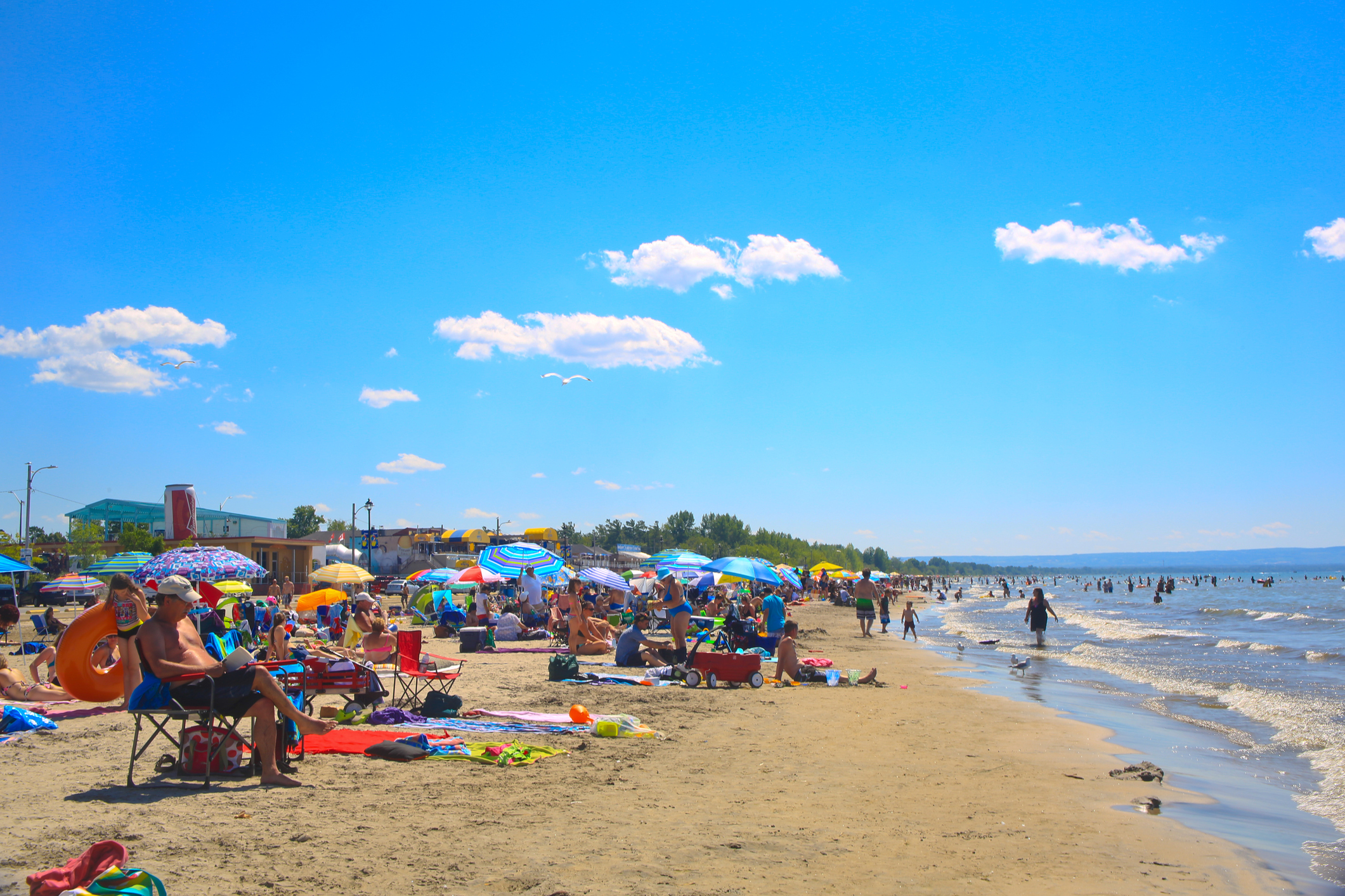 Wasaga Beach, Canada-July 22, 2916: Panoramic view with many people swimming, sunbathing, walking, on the beach on a lovely summer day.