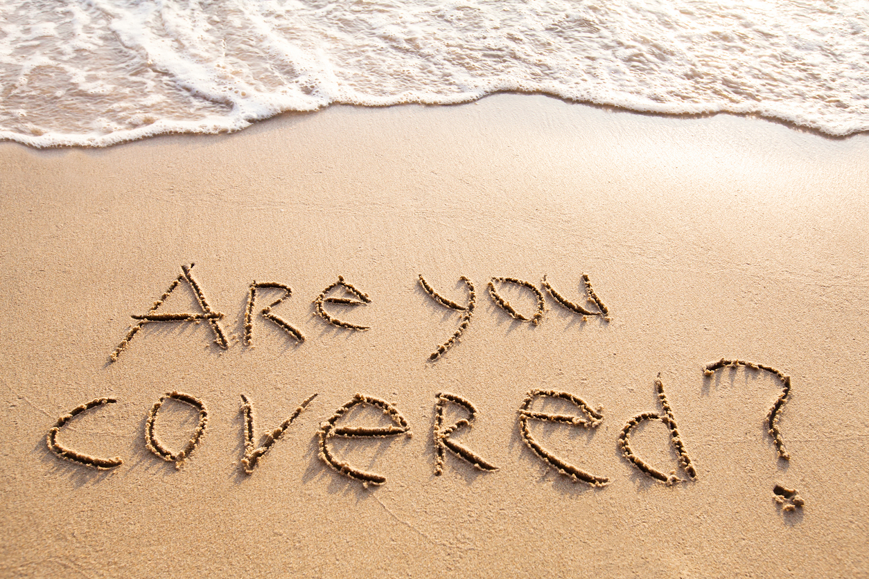 are you covered, travel insurance concept, text on sandy beach