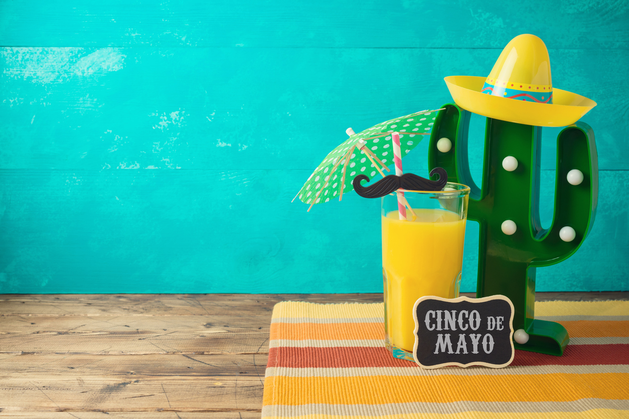 Cinco de Mayo holiday background with Mexican cactus, party sombrero hat and orange juice on wooden table